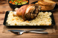 Roasted pork knuckle served with sauerkraut on the wooden background. Stock Photos