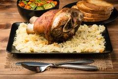 Roasted pork knuckle served with sauerkraut on the wooden background. Roasted pork knuckle served with sauerkraut on the brown wooden background Stock Photos