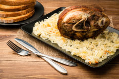 Roasted pork knuckle served with sauerkraut on the wooden background. Roasted pork knuckle served with sauerkraut on the brown wooden background Stock Images