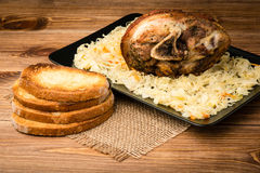 A roasted pork knuckle served with sauerkraut on the wooden background. A roasted pork knuckle served with sauerkraut on the brown wooden background Stock Photography