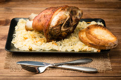 A roasted pork knuckle served with sauerkraut on the wooden background. A roasted pork knuckle served with sauerkraut on the  brown wooden background Royalty Free Stock Photo