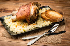 A roasted pork knuckle served with sauerkraut on the wooden rustic background. Stock Images