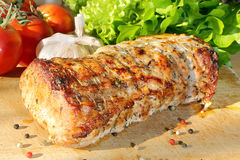 Roasted pork loin with herbs on wood background Stock Photos