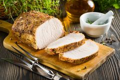 Roasted pork loin and ingredients on the table Stock Photos