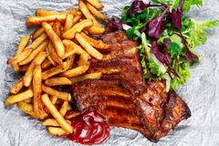 Roasted Pork Rib,  Fried Potato on white plate with Vegetables. Royalty Free Stock Image