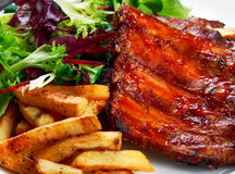 Roasted Pork Rib,  Fried Potato on white plate with Vegetables. Royalty Free Stock Photos