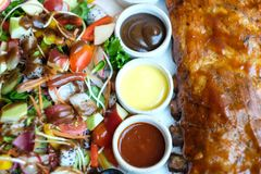 Roasted pork ribs with barbecue sauce and fruit salad. Served with three salad dressing stock photography