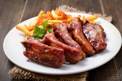 Roasted pork ribs and potato fries Royalty Free Stock Photos