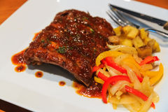 Roasted pork ribs with potato and salad Stock Photos