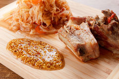 Roasted pork ribs with tomato, carrots and cabbage on a  cutting board Stock Photos