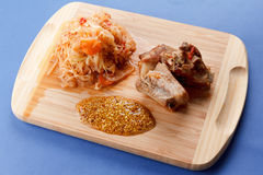 Roasted pork ribs with tomato, carrots and cabbage on a  cutting board Stock Image
