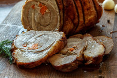 Roasted pork roll stuffed with vegetables on wooden board Stock Image
