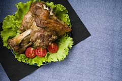 Roasted pork shank. Tomatoes and salad stock photography