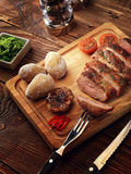 Roasted pork steak cut into slices on a wooden stand. Baked potato. The sauce of arugula. Salt shaker, pepper shaker. Knife for meat and meat fork Stock Photo