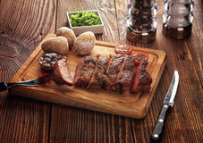 Roasted pork steak cut into slices on a wooden stand. Baked potato. The sauce of arugula. Salt shaker, pepper shaker. Knife for meat and meat fork Royalty Free Stock Images