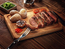 Roasted pork steak cut into slices on a wooden stand. Baked potato. The sauce of arugula. Salt shaker, pepper shaker. Knife for meat and meat fork Stock Photos