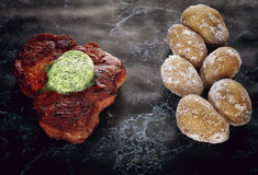 Roasted pork steak on a stone pedestal. Baked potato. Butter with herbs Royalty Free Stock Photography