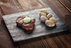 Roasted pork steak on a stone pedestal. Baked potato. Butter with herbs Stock Images