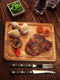 Roasted pork steak on a wooden stand. Baked potato. The sauce of arugula. Salt shaker, pepper shaker. Knife for meat and meat fork Royalty Free Stock Photos