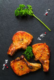 Roasted pork steaks, cutlets with bones  and fresh parsley on black stone background, top view Royalty Free Stock Photography