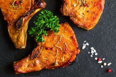 Roasted pork steaks, cutlets with bones  and fresh parsley on black stone background, top view Stock Photo