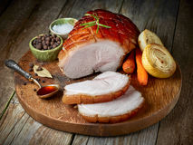 Roasted pork on wooden cutting board. Roasted pork on rustic wooden cutting board, top view Stock Image