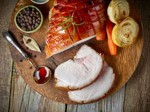 Roasted pork on wooden cutting board. Roasted pork on rustic wooden cutting board, top view Stock Photos