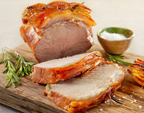 Roasted pork on wooden cutting board. Roasted pork slices on wooden cutting board, selective focus Stock Images