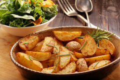 Roasted potato in brown bowl with fresh salad on wooden table Royalty Free Stock Image