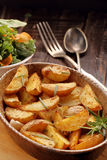 Roasted potato in brown bowl with fresh salad on wooden table Stock Photo