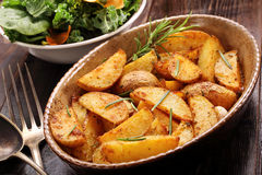 Roasted potato in brown bowl with fresh salad on wooden table Stock Photography