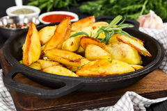 Roasted potato with fresh rosemary. In cast-iron pan Royalty Free Stock Images