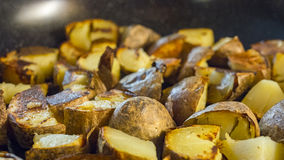 Roasted potato in a frying pan on wooden table. Alot of roasted potato in a frying pan on wooden table Stock Photos