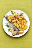 Roasted potato wedges and mackerel fish Stock Image