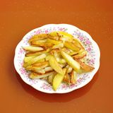 Roasted potatoes. On a plate on the orange  background Royalty Free Stock Images