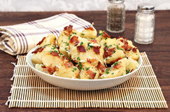 Roasted potatoes with bacon, parmesan and garlic. A bowl of roasted garlic, bacon and parmesan potatoes garnished with parsley bits royalty free stock images