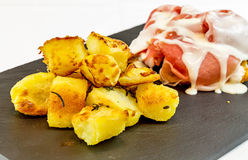 Roasted potatoes with ham and cream served black slate stone. Plate. Gourmet food stock image