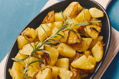 Roasted potatoes. Iwith onion and rosemary in a cast iron pan over a white chopping board on a blue table Royalty Free Stock Image