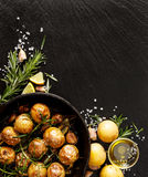 Roasted potatoes with rosemary, garlic, lemon and sea salt on a black background Stock Photography
