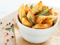 Roasted potatoes with rosemary in a white bowl Stock Images