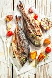 Roasted potatoes and seabream with herbs and tomatoes. On old table stock photo
