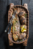 Roasted potatoes and trout fish with butter and herbs Stock Photo