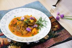 Roasted poultry liver,apple, curry sauce. On white plate with chive flower. Roasted poultry liver and apple piece in creamy curry sauce on white plate with royalty free stock photo