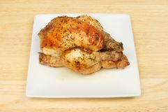 Roasted poussin on a plate. On a wooden tabletop Stock Images