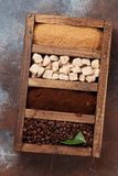 Roasted and powder coffee, brown sugar. Roasted beans, powder coffee and brown sugar in wooden box. Top view stock image