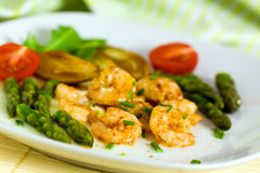 Roasted prawns with green asparagus and potato Stock Photo