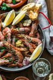 Roasted prawns shrimps in a pan with lemons, bread and wive Royalty Free Stock Images