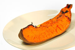 Roasted pumpkin. Piece of roasted pumpkin on white plate Royalty Free Stock Image