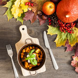 Roasted pumpkin with autumn leaves over wooden background Royalty Free Stock Images