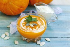 Roasted pumpkin and carrot soup with cream and pumpkin seeds on blue wooden background. Vegetarian autumn cream soup royalty free stock photography